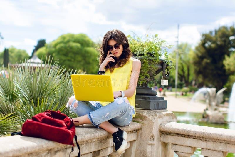 Menina moreno que trabalha com o portátil amarelo no verão no parque Está sentando-se na cerca, olhando ocupada foto de stock royalty free