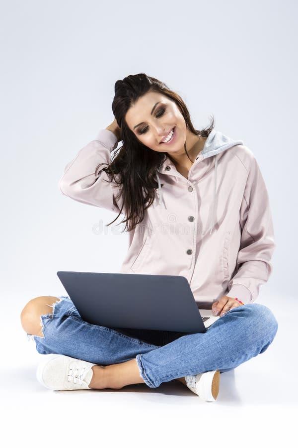 Menina moreno que trabalha com portátil quando assentar no assoalho com pés se cruzou foto de stock royalty free