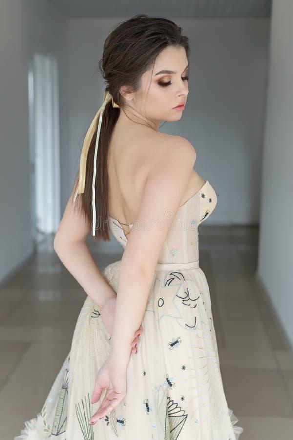 A menina moreno 'sexy' bonita no vestido elegante com o trem longo com alfazema floresce fotografia de stock royalty free