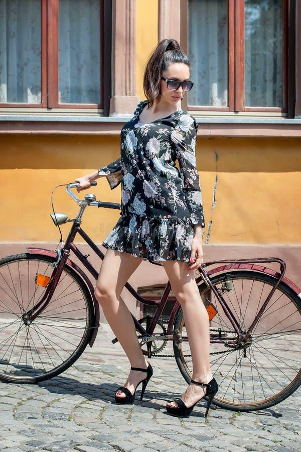 Menina moreno 'sexy' nova com a bicicleta retro velha do vintage do estilo fotografia de stock royalty free