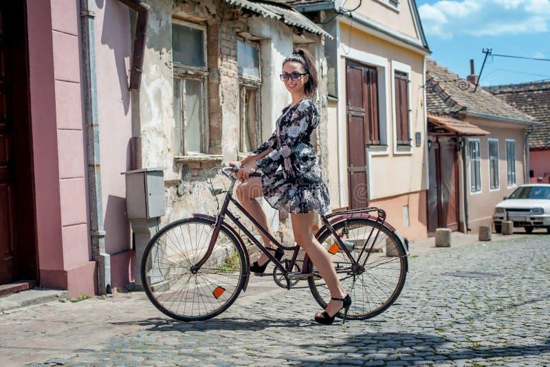 Menina moreno 'sexy' nova com a bicicleta retro velha do vintage do estilo foto de stock