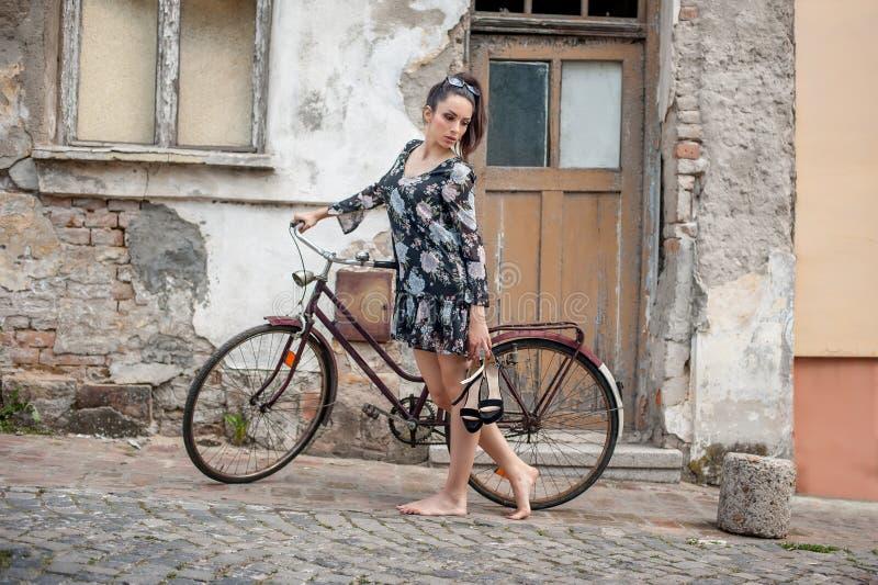 Menina moreno 'sexy' nova com a bicicleta retro velha do vintage do estilo imagem de stock royalty free