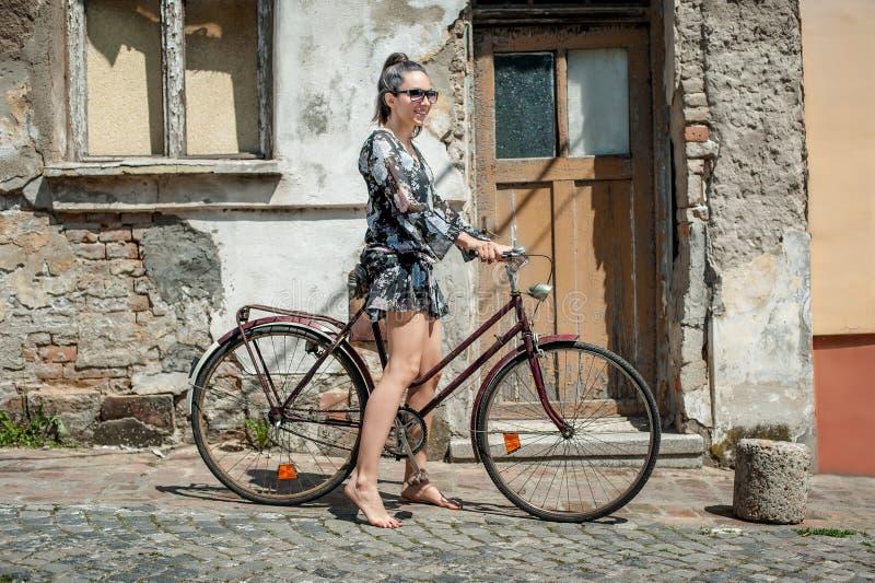 Menina moreno 'sexy' nova com a bicicleta retro velha do vintage do estilo foto de stock royalty free