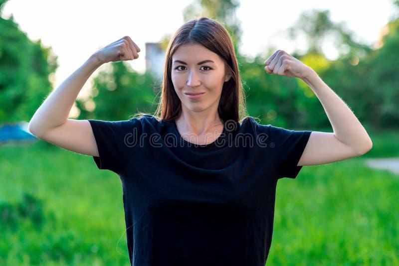 A menina moreno sorri felizmente verão no campo em um prado verde Mãos que mostram os bíceps As emoções são gracejos fêmeas fotografia de stock