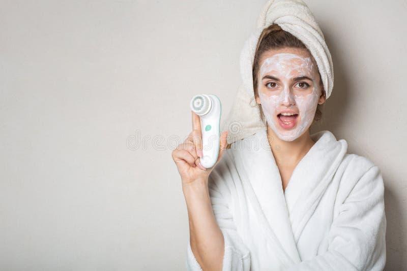 Menina moreno surpreendida que levanta com o líquido de limpeza de creme hidratando da máscara e da cara Espaço vazio fotos de stock