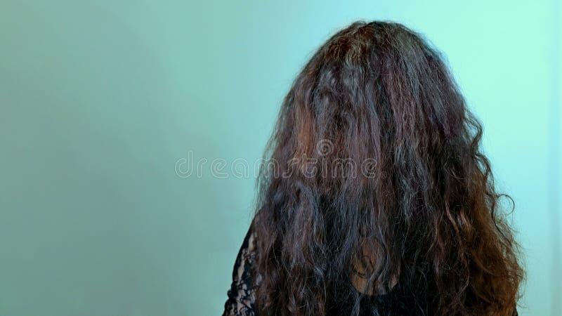 Menina moreno terrível com o cabelo escuro longo que cobre sua cara Cena do horror do conceito, cartaz de Dia das Bruxas, barbear imagens de stock