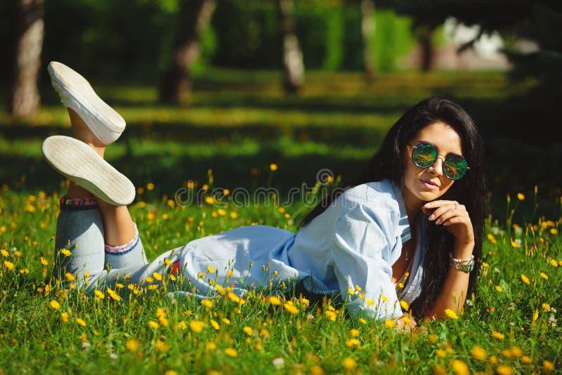 A menina moreno veste em volta dos óculos de sol, encontra-se na grama verde do verão fotografia de stock