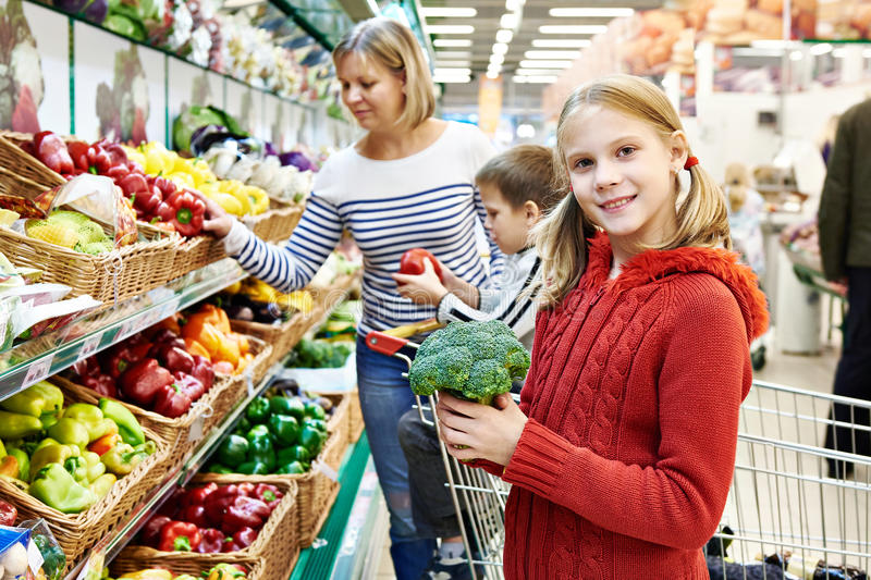 A menina mostra brócolis no supermercado fotos de stock royalty free