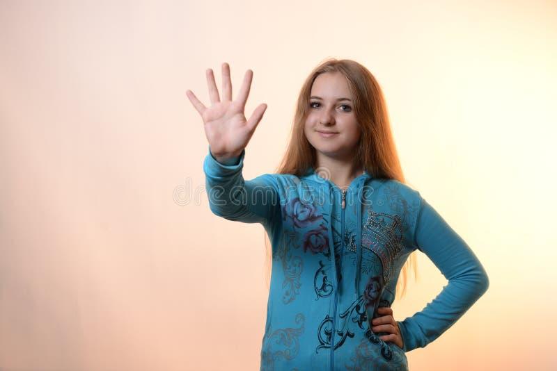 A menina mostra cinco imagens de stock