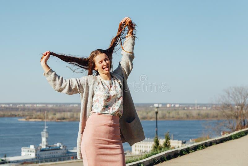 A menina mostra a l?ngua com uma boca aberta e aumenta o cabelo imagens de stock royalty free