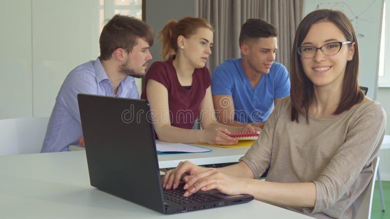 A menina mostra o polegar acima na tabela com portátil imagens de stock royalty free