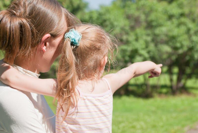 A menina mostra a sua matriz um dedo ao lado fotos de stock