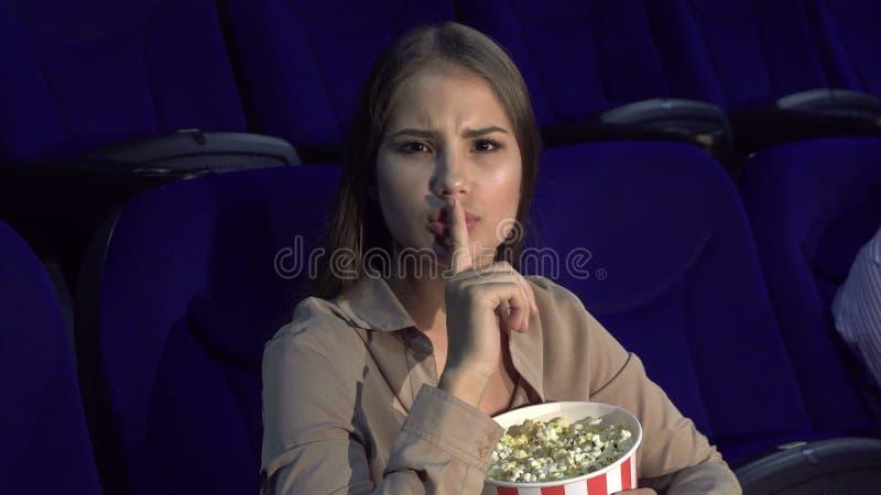 A menina mostra um sinal do silêncio que senta-se no salão do cinema imagem de stock royalty free