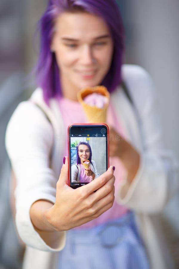 A menina mostra uma foto no telefone fotos de stock royalty free