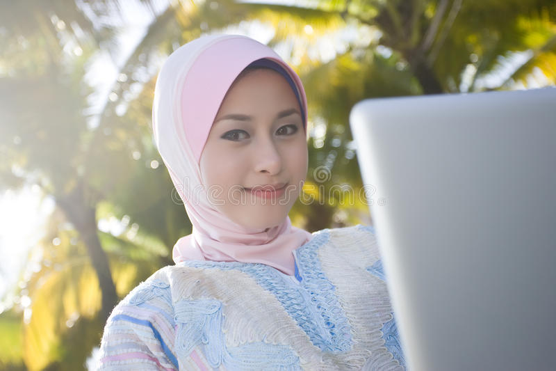 A menina muçulmana está usando o portátil imagens de stock