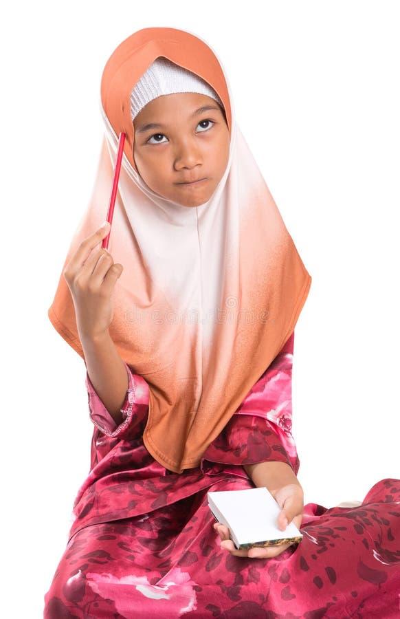 Menina muçulmana nova com lápis e bloco de notas V foto de stock