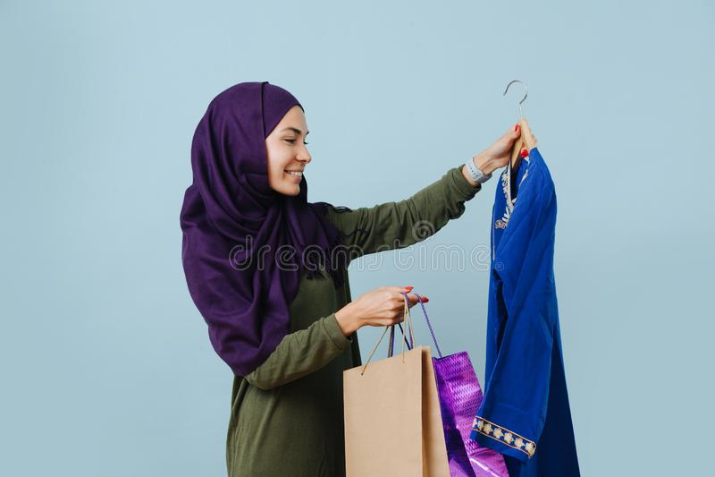 Menina muçulmana sorrindo de roupa casual escolhe um vestido de festa fotografia de stock