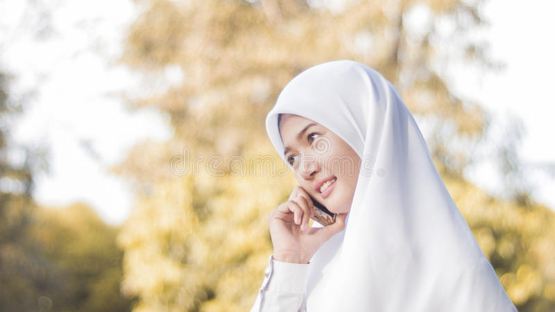 A menina muçulmana tem o telefone celular foto de stock