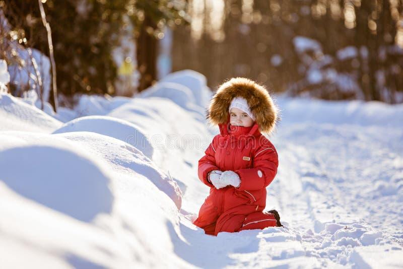 A menina muito bonito pequena em um terno vermelho com capa da pele senta-se no sno fotos de stock royalty free