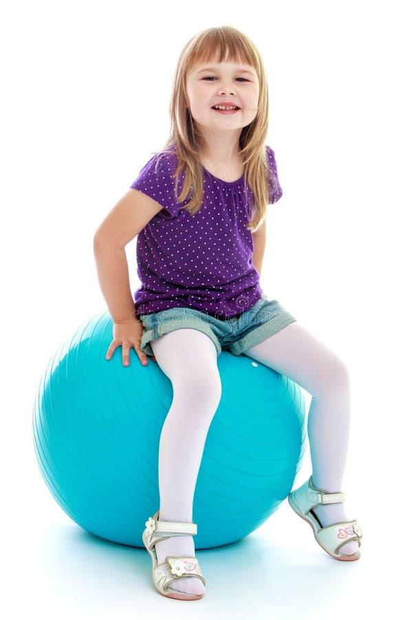 A menina muito bonito que senta-se em uma bola grande ostenta fotos de stock royalty free