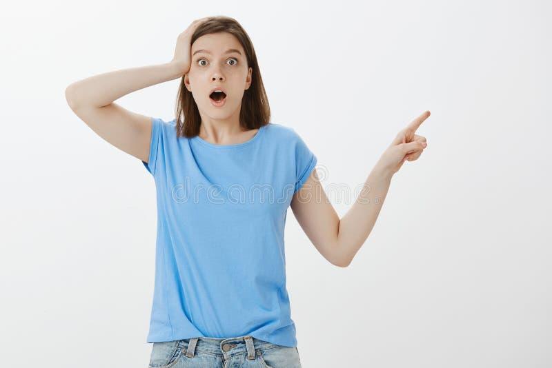 A menina não pode acreditar que aquela lhe aconteceu Retrato da mulher atrativa confusa surpreendida no t-shirt azul, guardando a foto de stock