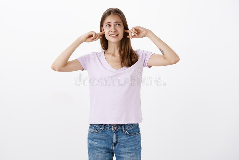 A menina não pode fazer trabalhos de casa em tal ruído Fêmea incomodada intensa desagradada com tatuagem que aperta os dentes que imagem de stock