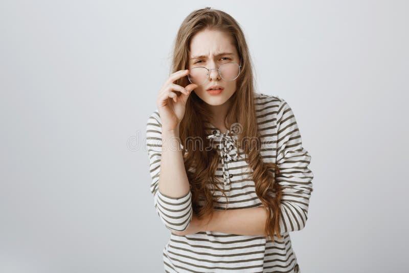 A menina não pode ver claramente sem vidros Adolescente novo bonito que é vesgo e que olha de sobrancelhas franzidas, tendo a vis imagens de stock royalty free