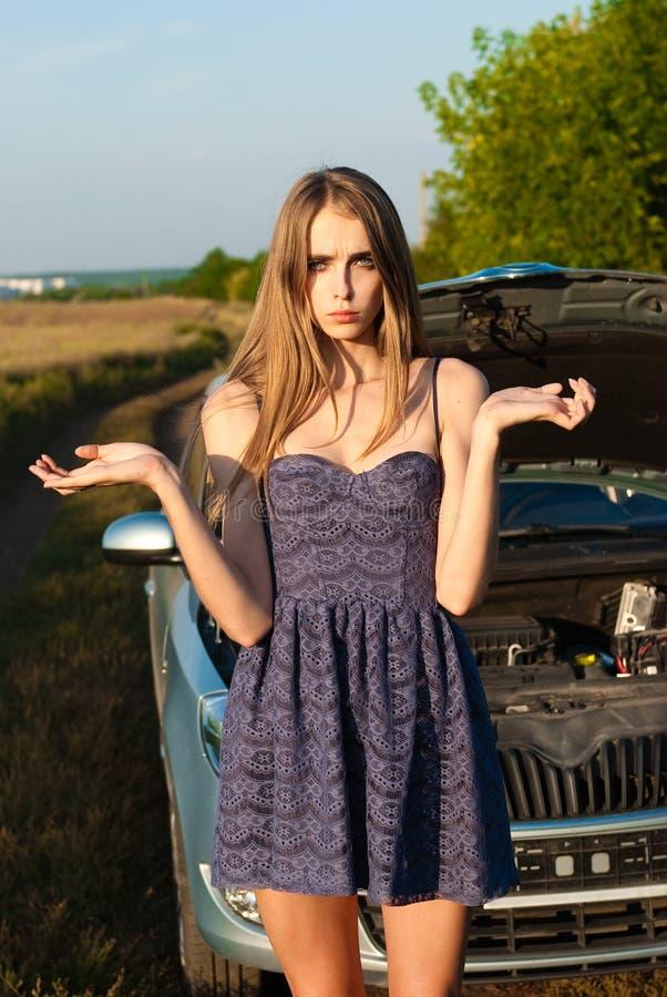 A menina não soube o que fazer com um carro que quebrasse fotografia de stock royalty free