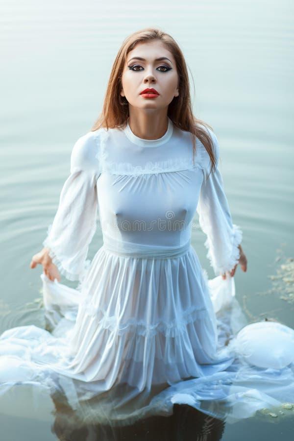 Menina na água ereta da noiva branca do vestido fotografia de stock royalty free