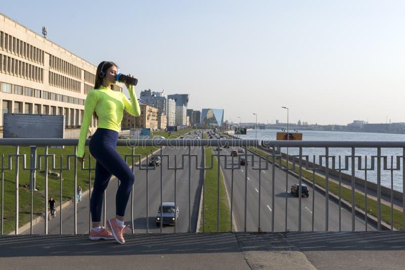 Menina na água potável da roupa dos esportes na ponte sobre a estrada com os carros na cidade foto de stock