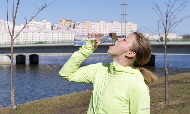 Menina na água potável superior dos esportes verdes de uma garrafa no fundo das construções do canal, atleta foto de stock