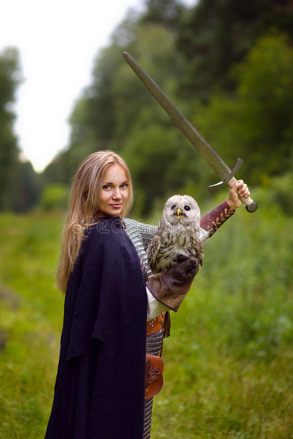 A menina na armadura com coruja guarda uma espada aumentada imagem de stock
