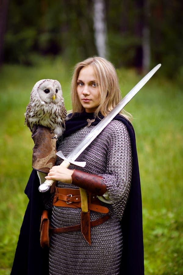 Menina na armadura e com uma espada que guarda uma coruja imagens de stock