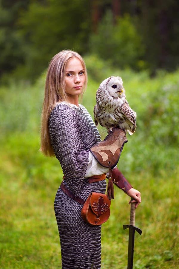 Menina na armadura e com uma espada que guarda uma coruja fotografia de stock