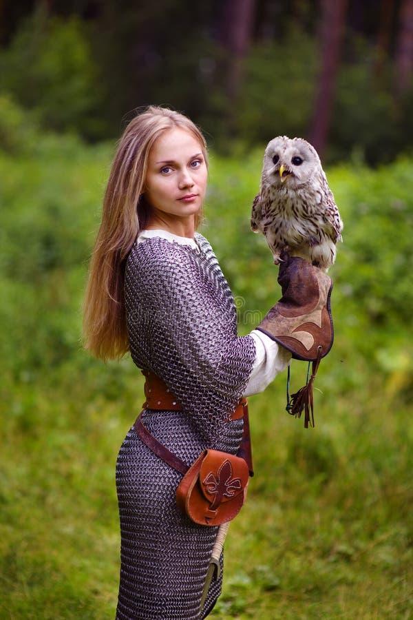 Menina na armadura que guarda uma coruja foto de stock