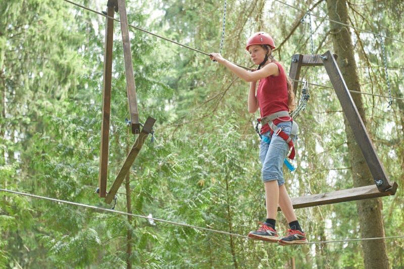 Menina na atividade de escalada no fio alto Forest Park fotografia de stock royalty free