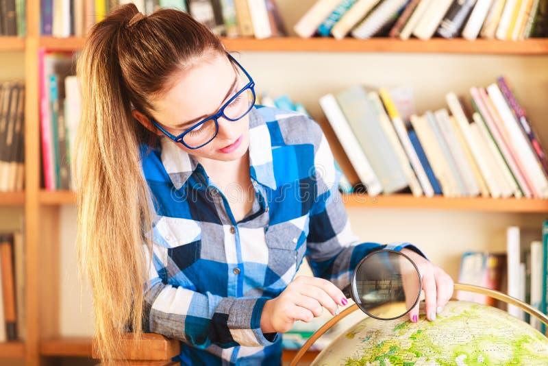 Menina na biblioteca que aponta ao globo fotos de stock