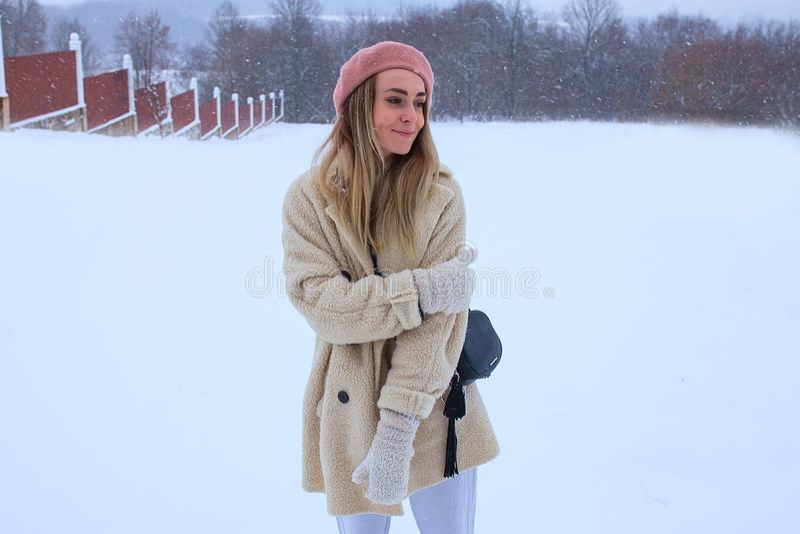 A menina na boina cor-de-rosa está estando na neve e no sorriso imagens de stock royalty free