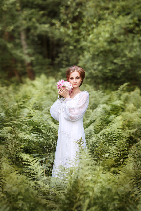 menina na borda da floresta em um vestido branco longo imagem de stock royalty free