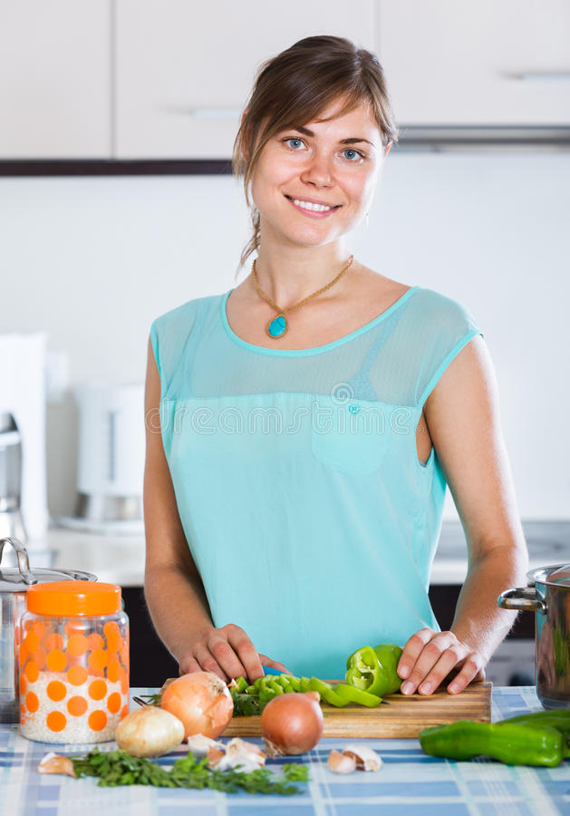 Menina na caçarola e nos vegetais da cozinha fotos de stock