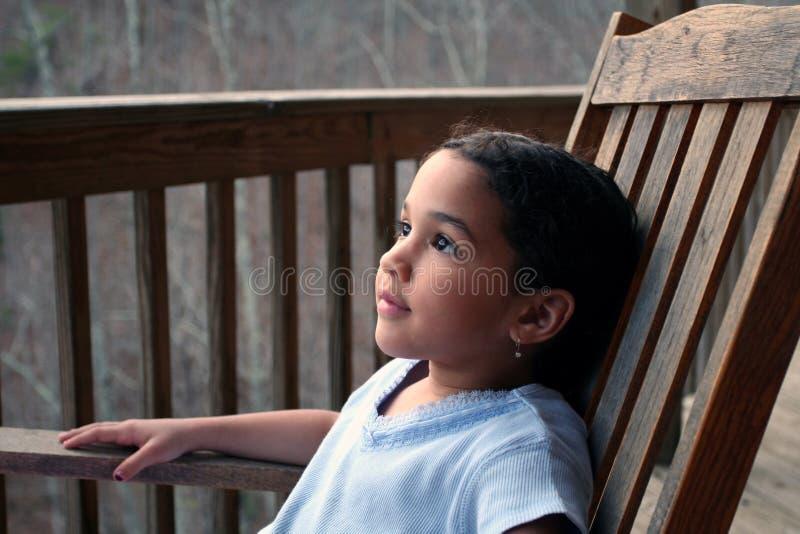 Menina na cadeira de balanço imagem de stock