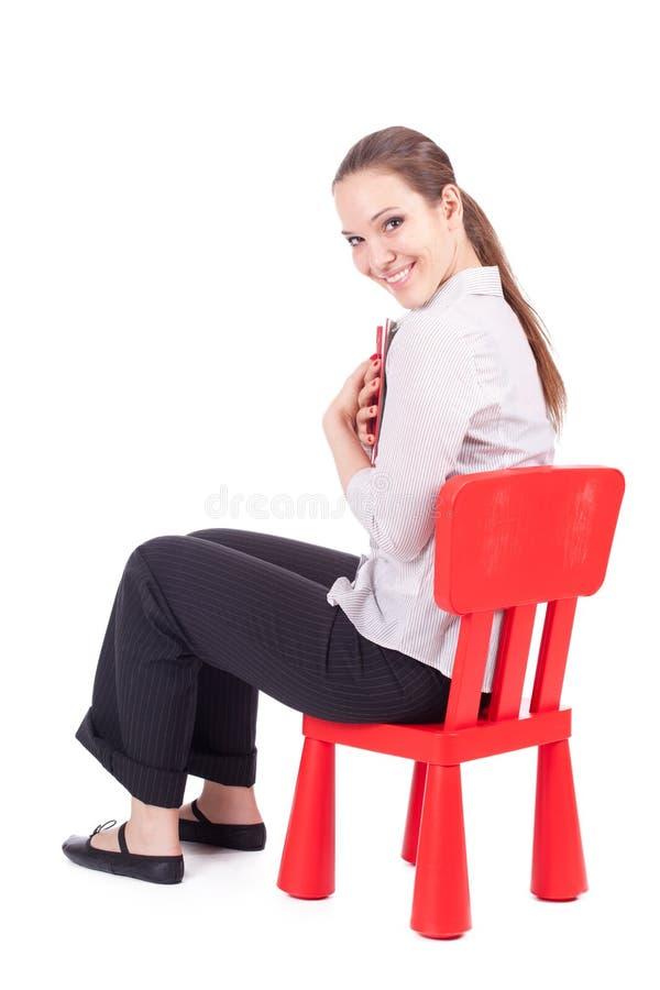 Menina na cadeira vermelha pequena fotografia de stock royalty free