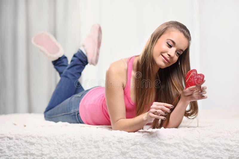 Menina na cama com coração vermelho imagens de stock
