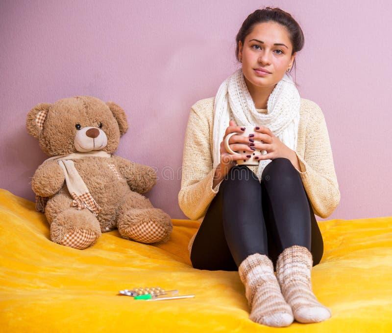 Menina na cama com um urso de peluche com copo à disposição imagem de stock