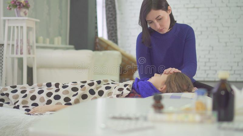 A menina na cama tem um frio em casa, uma tosse forte, verificando a temperatura de sua mãe imagens de stock