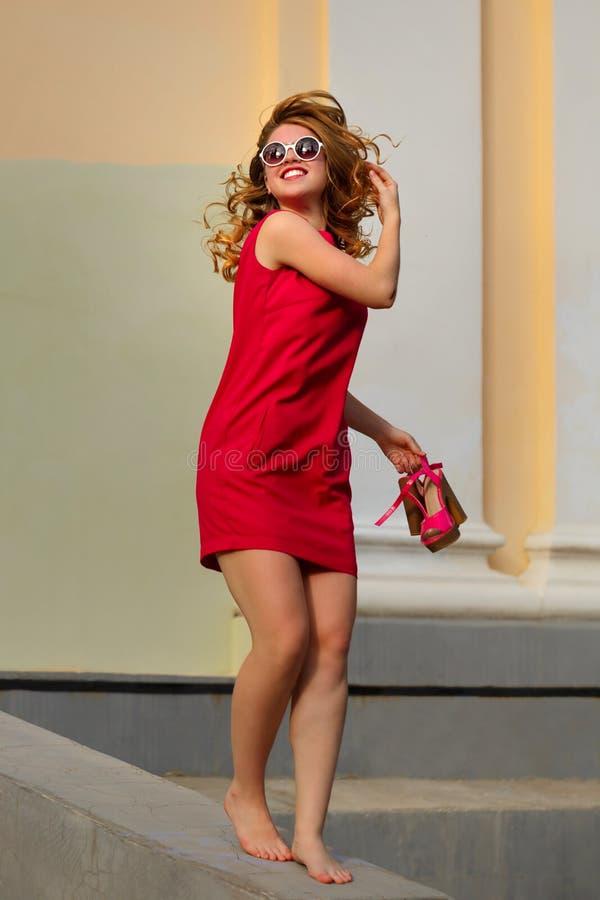 Menina na caminhada vermelha do vestido com os pés descalços fotos de stock royalty free