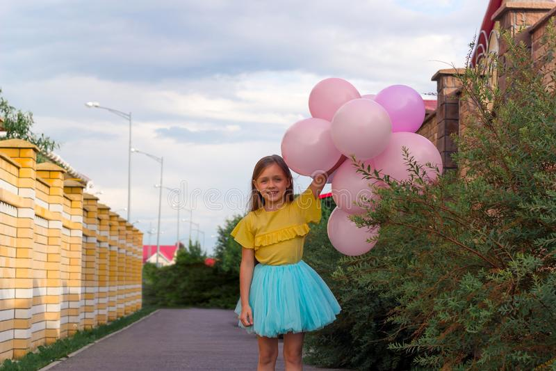 menina na camisa amarela e na saia azul que sorri e que guarda muitos balões, infância feliz e conceito do verão fotografia de stock