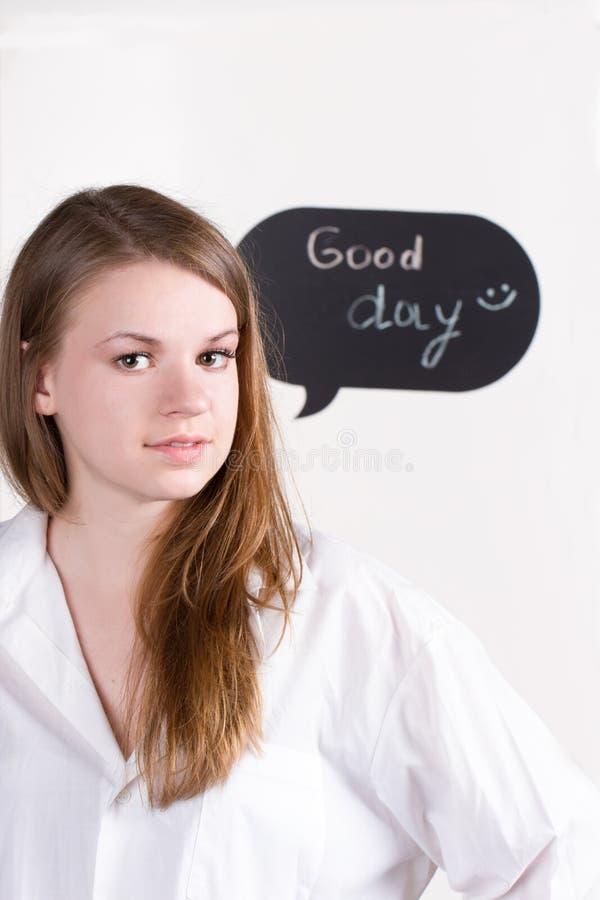 Menina na camisa branca no fundo da inscrição um o bom dia fotos de stock royalty free