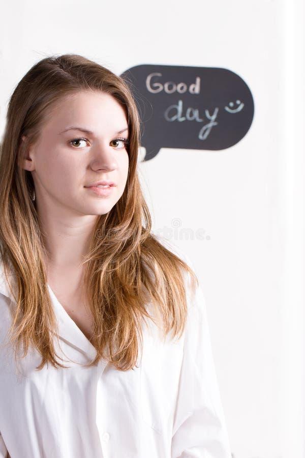 Menina na camisa branca no fundo da inscrição um o bom dia foto de stock royalty free