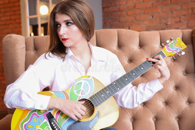 Menina na camisa branca que levanta com uma guitarra no estilo da hippie imagens de stock